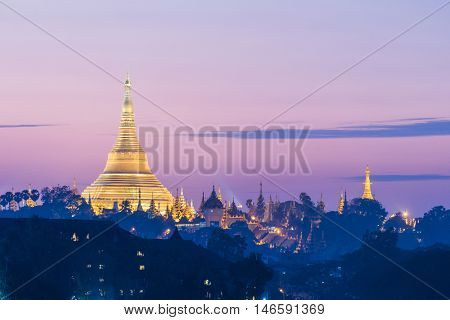 Shwedagon Paya is the most sacred golden buddhist pagoda in Myanmar.  It is located on the Singuttara hill in Yangon, Myanmar. Sunset time on this picture