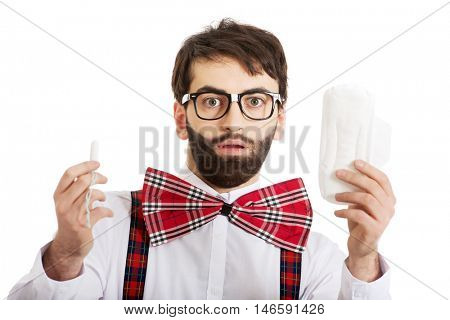 Shocked man holding menstruation pad.