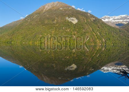 Mirror Lakes are a famous natural landmark omn the Milford Road in the Fiordland National Park. Snowy mountains are reflecting in a calm water. New Zealand