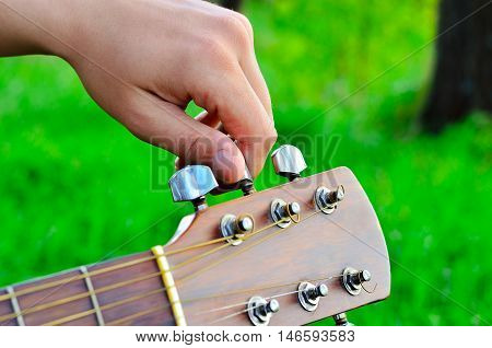 Man adjusts the guitar strings in the open air
