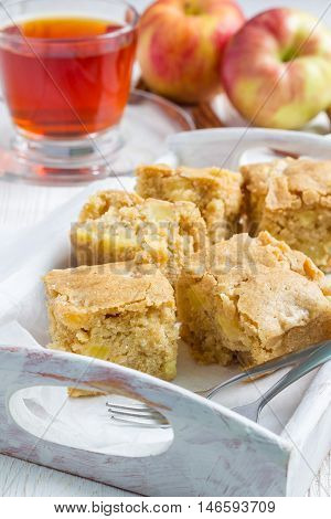 Homemade blondie (blonde) brownies apple cake square slices in wooden tray vertical