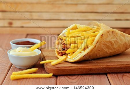Gyro with chicken and french fries on a wooden board next to the ketchup and mayonnaise