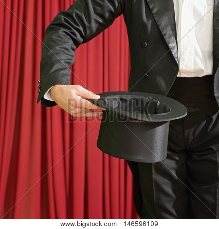 Magician holding top hat on stage, color image