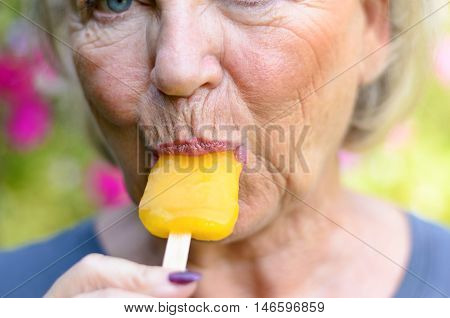 Senior Woman Sucking On An Iced Orange Lolly