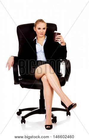 Tired business woman sitting on wheel chair with cup of coffee