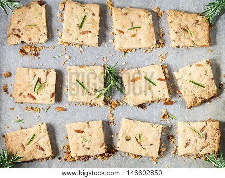 Freshly baked butter cookies with rosemary, pine nuts and pistachio on baking parchment, decorated with rosemary sprigs. Top view