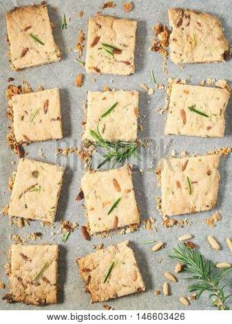 Butter cookies with rosemary, pine nuts and pistachio on baking parchment, decorated with rosemary sprigs. Vertical image