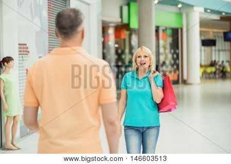 Happy mature woman is meeting her husband in shopping center. She is carrying packet and smiling