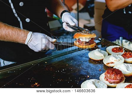 Cook preparing burgers at the barbecue outdoors