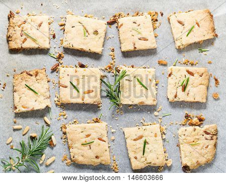 Butter cookies with rosemary, pine nuts and pistachio on baking parchment, decorated with rosemary sprigs