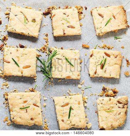 Butter cookies with rosemary, pine nuts and pistachio on baking parchment, decorated with rosemary sprigs. Square image. Top view