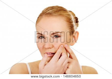 Unhappy young woman squeezing pimple on face