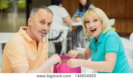 Mature man is giving to his wife a gift. Woman is opening packet with surprise. They are looking at camera and smiling