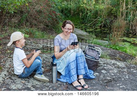 Grandmother reading to her grandson funny e-book reader outdoors