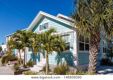 Blue Bungalow and Palm Trees under blue sky