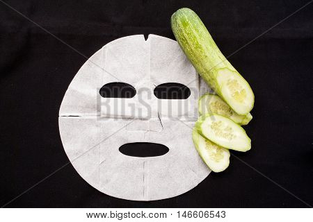 natural sheet mask extracts from cucumber for the face skin care on background black