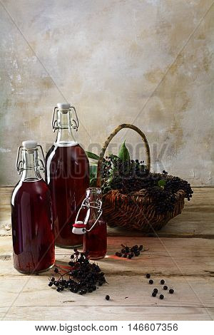 bottles with the red juice from black elderberries (Sambucus nigra) and a basket with berries on rustic wood planks in front of a vintage wall with copy space vertical selected focus