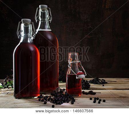bottles with red juice of black elderberries (Sambucus nigra) and some berries on rustic wooden planks dark background with copy space