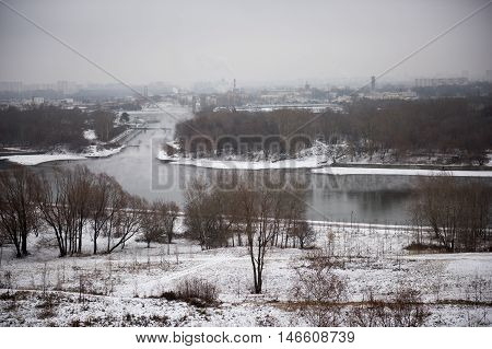 River fog at dawn. winter panorama near the river Russia. Winter landscape of snow-covered fields trees and river in the early misty morning. Thermal power plant with smoking chimneys on the river / ecology.