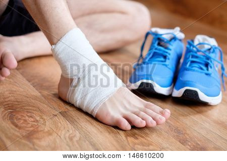 Sportsman Massaging His Injured Ankle After A Sport Accident