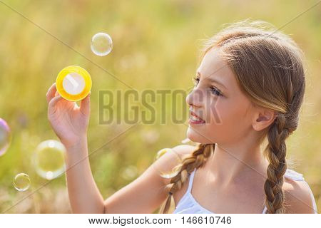 Happy female kid is having fun with soap bubbles on meadow. She is looking at flying ball and smiling