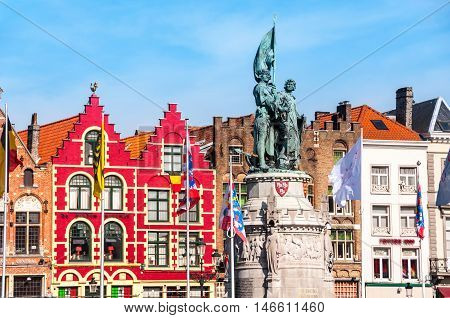 Famous old colorful buildings at Market square in Bruges Belgium. Popular Flemish city with almost intact medieval architecture. Statue of Jan Breydel and Pieter de Coninck.