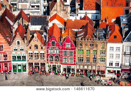 Famous old colorful buildings at Market square in Bruges Belgium. Popular Flemish city with almost intact medieval architecture. Motion blurred people