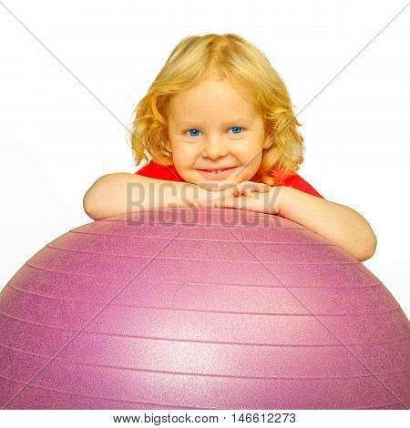Sporting child with big ball. Kids` gym and fitness.