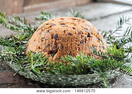 Christmas plum pudding on fir a branches.