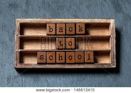 Back to school conceptual image. Vintage blocks with text, retro style pencil in wooden box. Gray stone background, macro