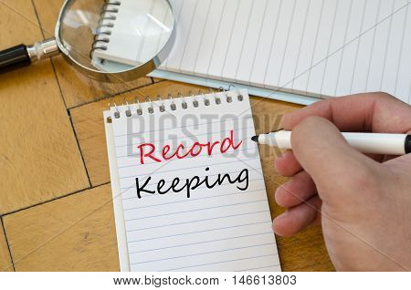 White notepad and human hand on the wooden background