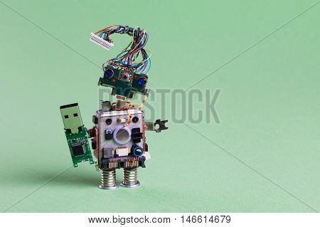 Retro robot with usb flash storage stick. storing concept, stylish computer character blue eyed head, electrical wire hairstyle. Copy space, green background