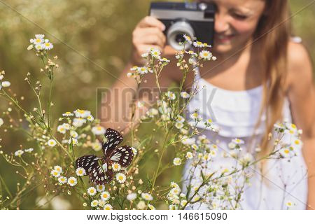 Joyful kid is taking photos of butterfly sitting on daisy. She is standing on meadow and laughing. Focus on insect