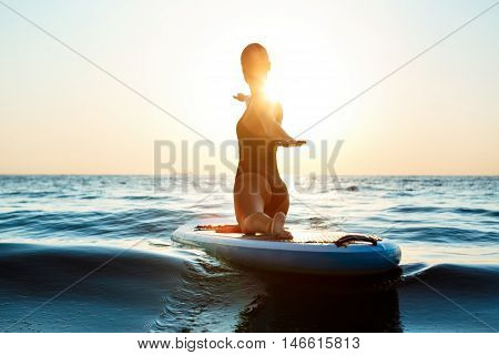 Silhouette of young beautiful girl practicing yoga on surfboard in sea at sunrise.