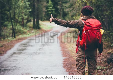 Woman with red backpack hitchhiking alone on the road Travel Lifestyle concept rear view