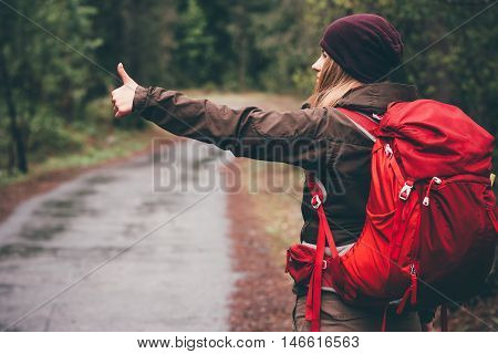 Woman Traveler Hitchhiking with red backpack alone on the road rainy day Travel Lifestyle concept rear view