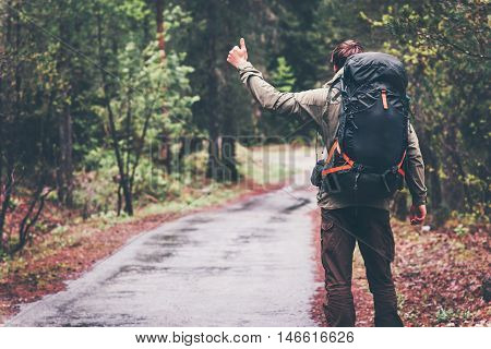 Man Traveler with backpack Hitchhiking alone on the road Travel Lifestyle concept rear view