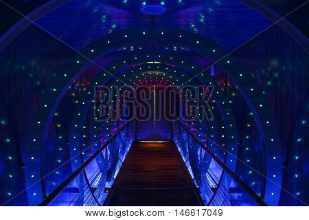 Bar Harbor, USA - October 15, 2015: Walkway as a tunnel with multiple colored lights and a door at the end, picture was taken on the cruise ship AIDA Diva