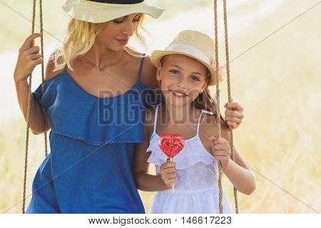 Carefree girl is swinging with her mother in nature. She is eating candy and smiling. Woman is embracing and looking at child with love