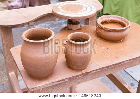 two freshly made clay vases on the worktable of a potter