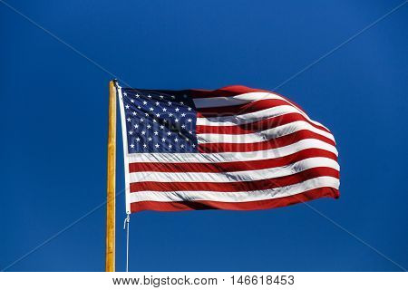 American flag with stars and stripes fluttering in blue sky