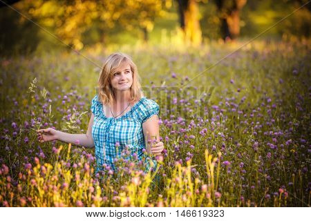 Beauty woman in the Meadow. Beautiful Young Woman Outdoors. Enjoy Nature. Healthy Smiling womanl lying on Green Grass with wild Flowers. Laughing And Happy