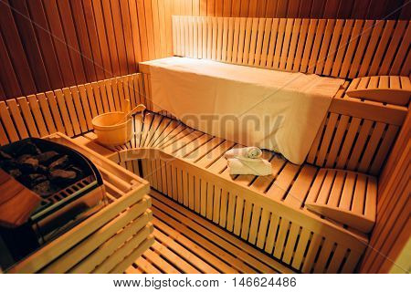 Empty wooden sauna room with towels ladle bucket ready to be used