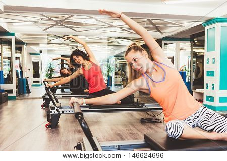 Young women exercising on pilates reformers beds. Focus is on the background.