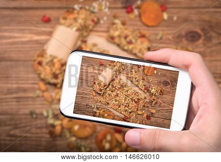 Hands taking photo homemade energy bars with smartphone.