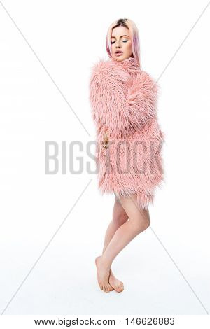 Young girl model with pretty sexy face and pink hair has bright professional fashion eyeshadow wearing pink fur coat