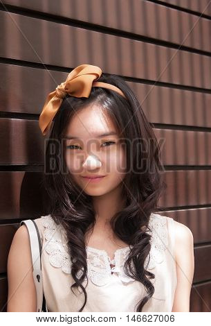 Outdoor portrait of attractive asian woman smiling in white dress against wooden lath wall background