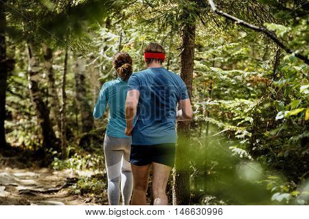 runners woman and man run one behind another in woods. back men sweat