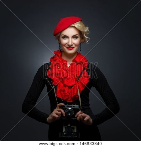 Beautiful young woman in red beret holding retro photo camera. Happy expression. Red lips. Over black background. Copy space.
