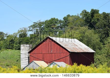a old red barn beside a white silo.
